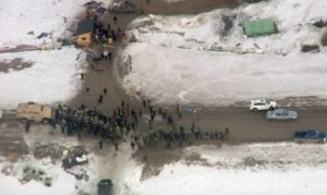 In this Wednesday, Feb. 1, 2017, aerial image taken from a video by KXMB in Bismarck, N.D., law enforcement officers line up against protesters during the eviction of about 40 Dakota Access pipeline opponents from a camp on private property owned by the pipeline developer where the protesters set up on higher ground near their flood-prone main camp in southern North Dakota near Cannon Ball, N.D. Maj. Gen. Malcolm Frost says the Army is following the steps outlined in President Donald Trump's order earlier this month for a fast review of requests to approve the pipeline. (KXMB via AP)
